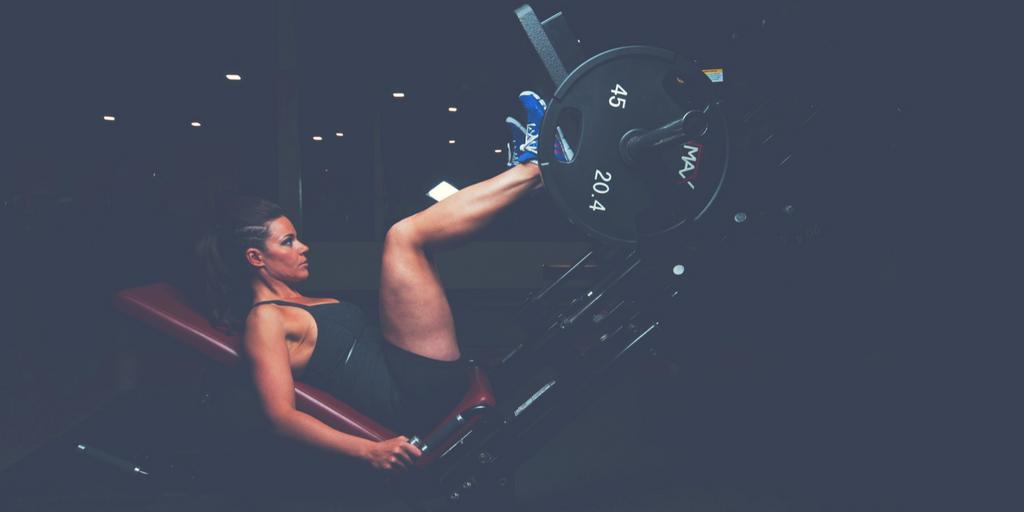 Kobieta trenująca nogi na suwnicy na siłowni